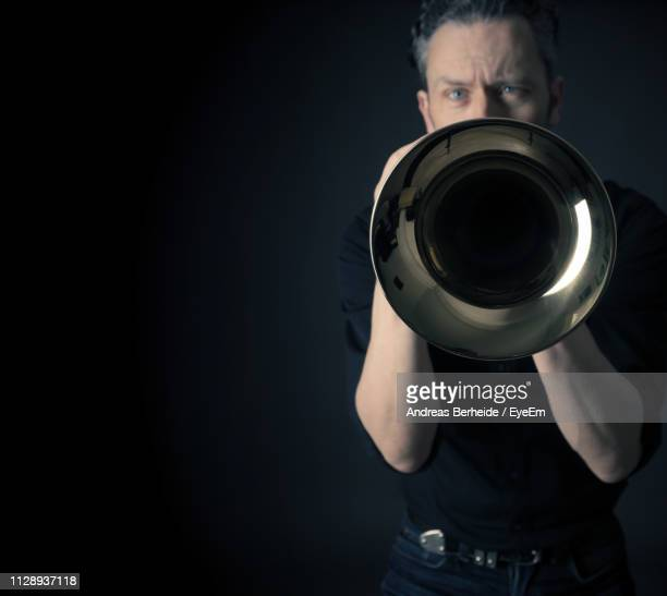 portrait of man playing trumpet against black background - tromba foto e immagini stock