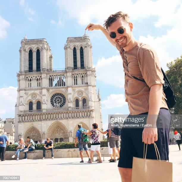 portrait of man pointing at notre dame - french culture stock photos and pictures