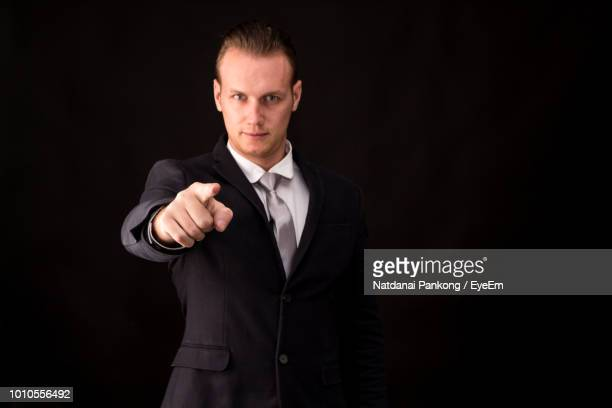 Portrait Of Man Pointing While Standing Against Black Background