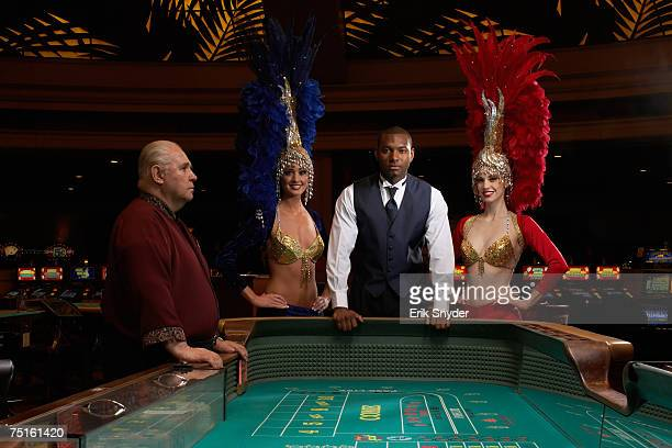Portrait of man posing at roulette table with two dancers and senior casino worker