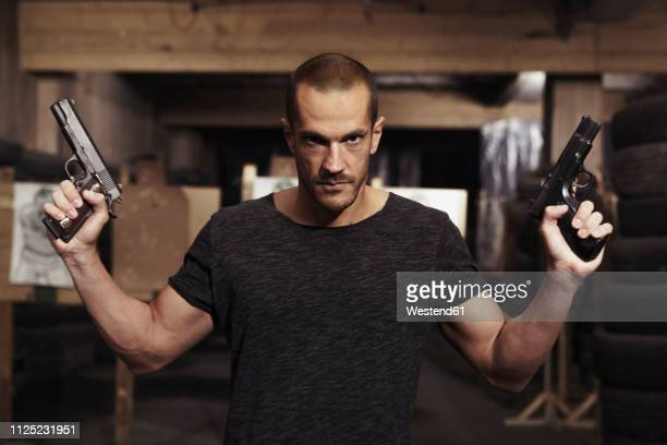 portrait of man posing with two guns in an indoor shooting range - murder stock pictures, royalty-free photos & images