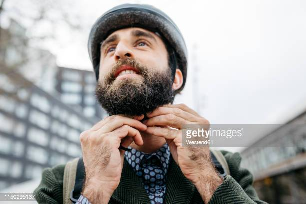 portrait of man putting on bicycle helmet in the city - cycling helmet stock pictures, royalty-free photos & images
