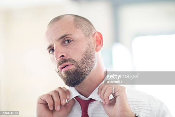 Portrait of man putting on his tie