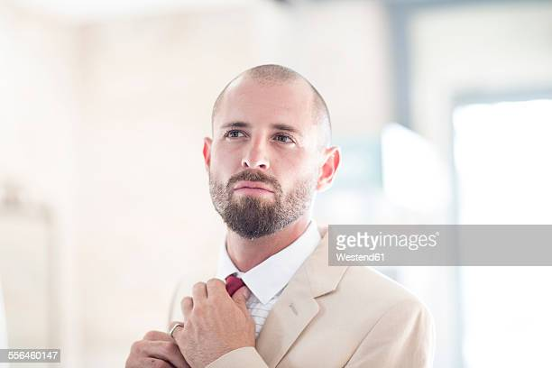 portrait of man putting on his tie - arrogance stock pictures, royalty-free photos & images
