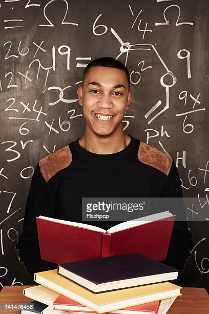 Portrait of man reading books in school class