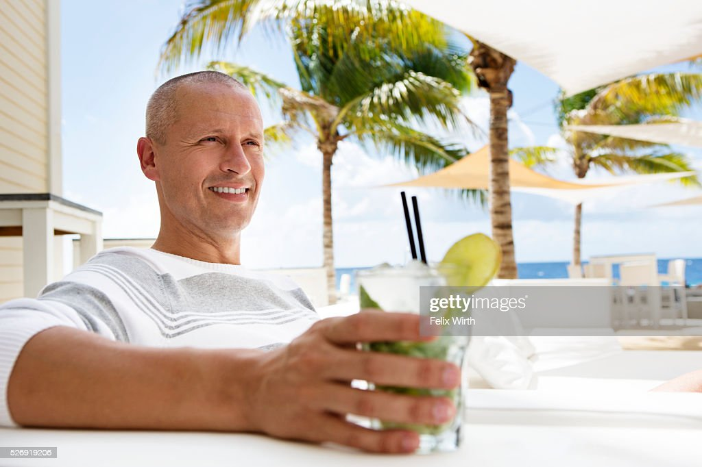 Portrait of man relaxing at cafe nearby beach : Stockfoto