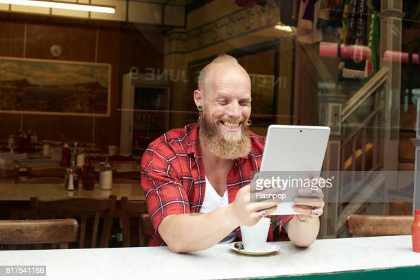 Portrait of man relaxing in a cafe using a digital tablet