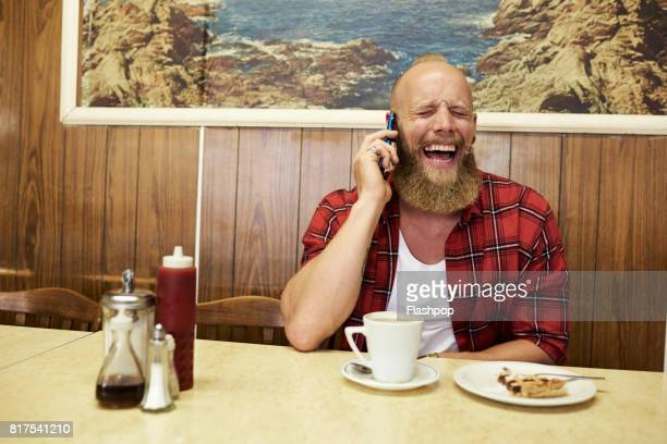 Portrait of man relaxing in a cafe using phone