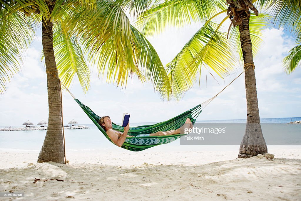 Portrait of man relaxing in hammock on beach reading book : Stockfoto