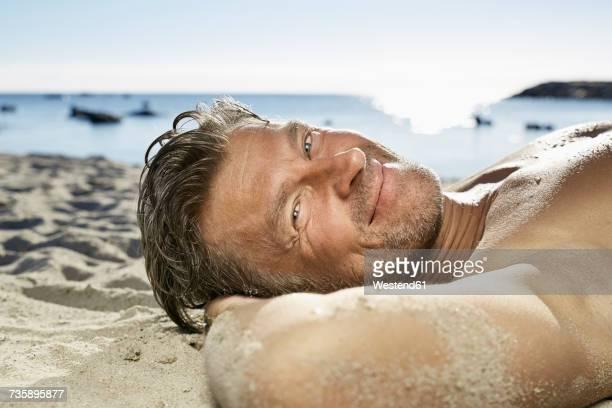 Portrait of man relaxing on sandy beach