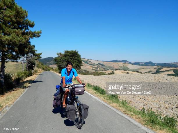 Portrait Of Man Riding Bicycle On Road Against Clear Sky