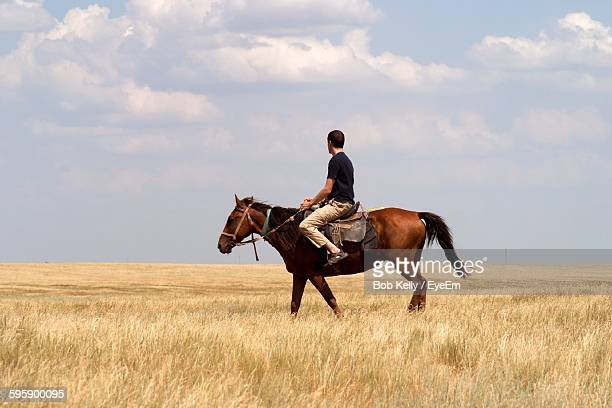 Portrait Of Man Riding Horse On Field Against Cloudy Sky
