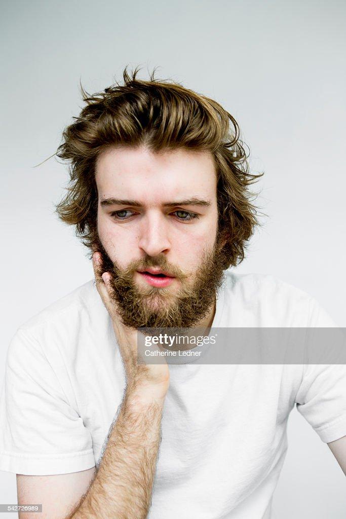 Portrait of man rubbing beard : Stock Photo
