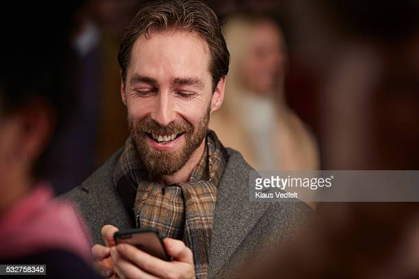 Portrait of man scrolling on phone among crowd