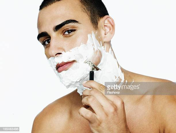 Portrait of man shaving his face