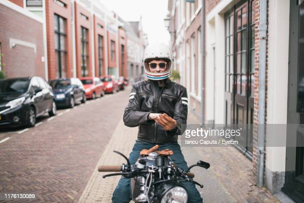 portrait of man siting on motorcycle at street in city - only mid adult men stock pictures, royalty-free photos & images