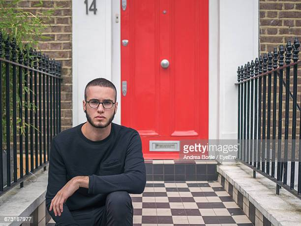 Portrait Of Man Sitting Against Red Door