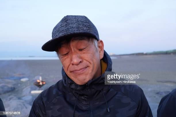 Portrait of man sitting at beach shut eye on the morning glow coast.