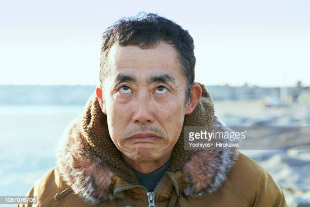 Portrait of man sitting at beach with strange expression on the morning glow coast.