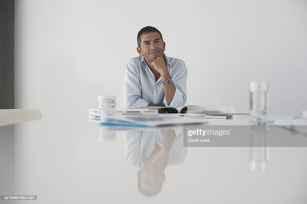 Portrait of man sitting at table in office : Stockfoto