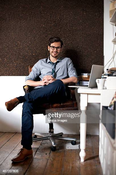 Portrait of man sitting by desk