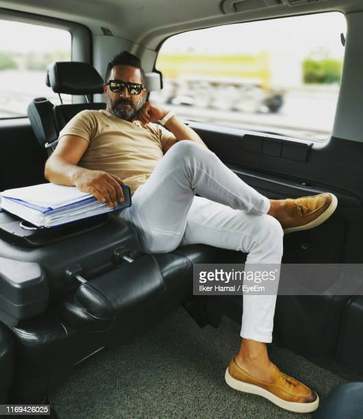 portrait of man sitting by files in car - middle east stock pictures, royalty-free photos & images