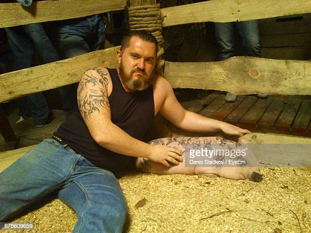 Portrait Of Man Sitting By Pig In Barn