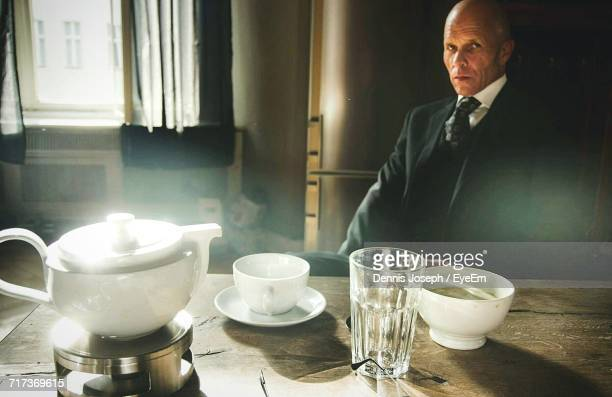 Portrait Of Man Sitting By Table With Tea Cup And Teapot At Home