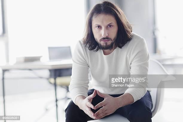 Portrait of man sitting in chair in design studio