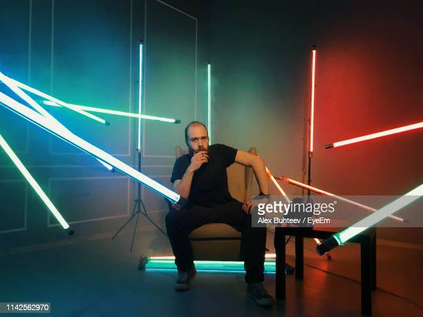 portrait of man sitting in illuminated room - fluorescent light stock pictures, royalty-free photos & images
