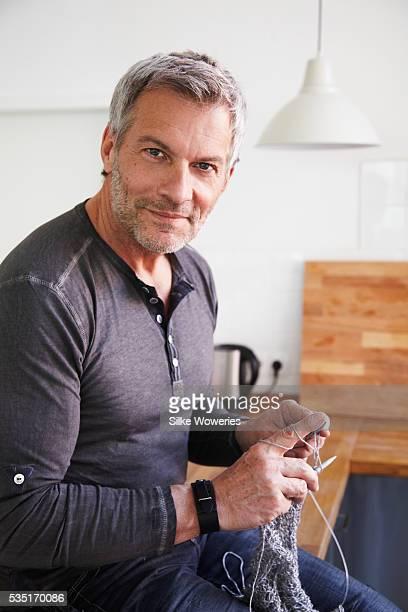 Portrait of man sitting in kitchen and knitting woolen jumper
