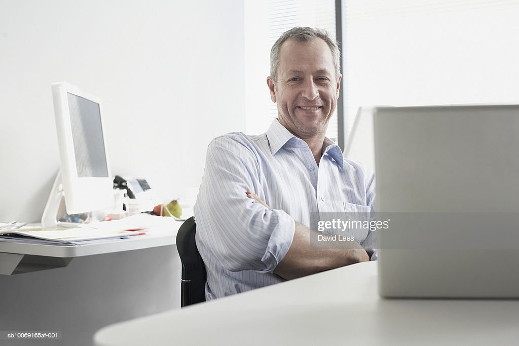 Portrait of man sitting in office : Stockfoto