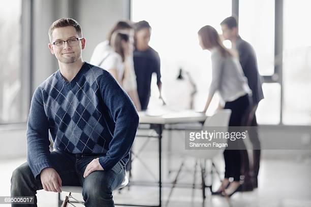 Portrait of man sitting in open studio room