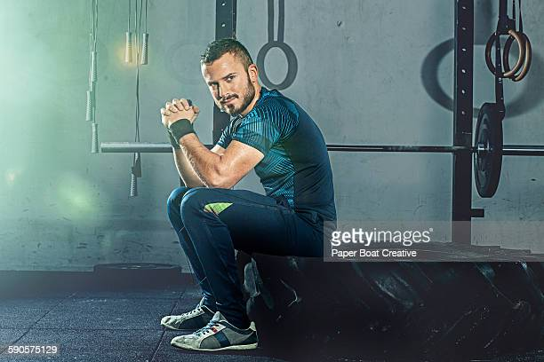 Portrait of man sitting on a giant gym tire