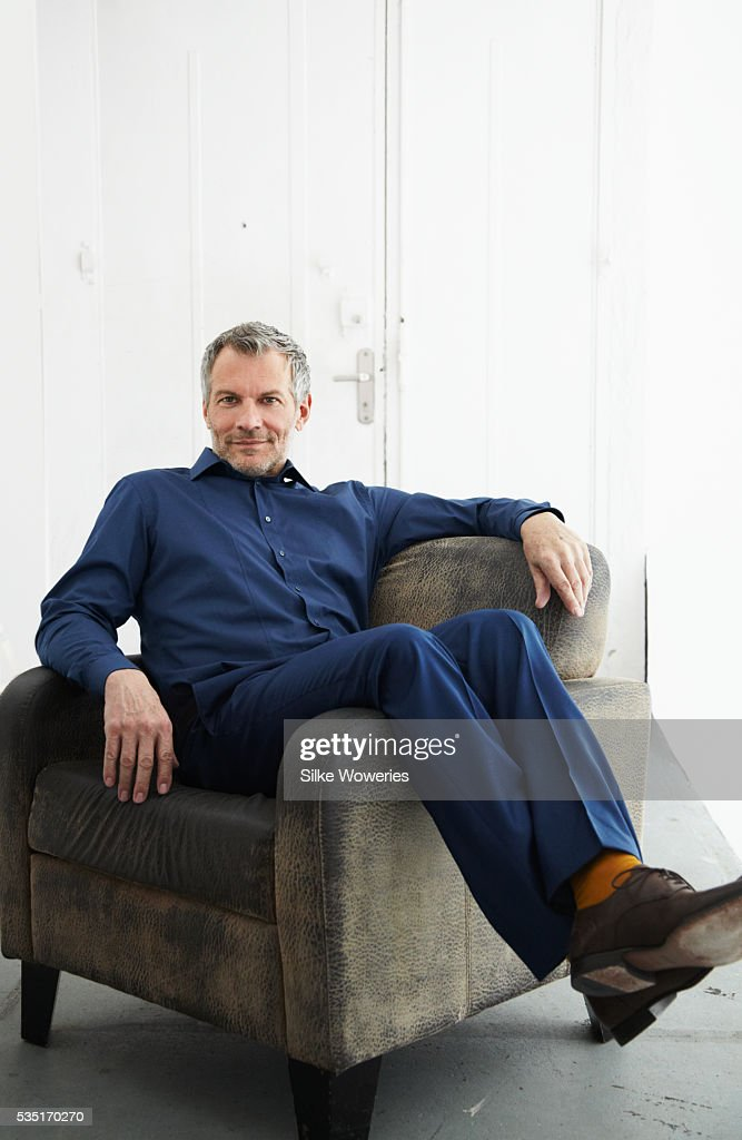 Portrait of man sitting on armchair and relaxing : Foto de stock
