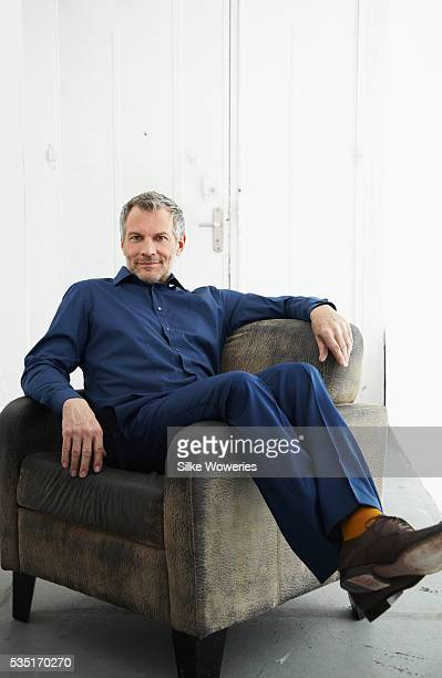 Portrait of man sitting on armchair and relaxing