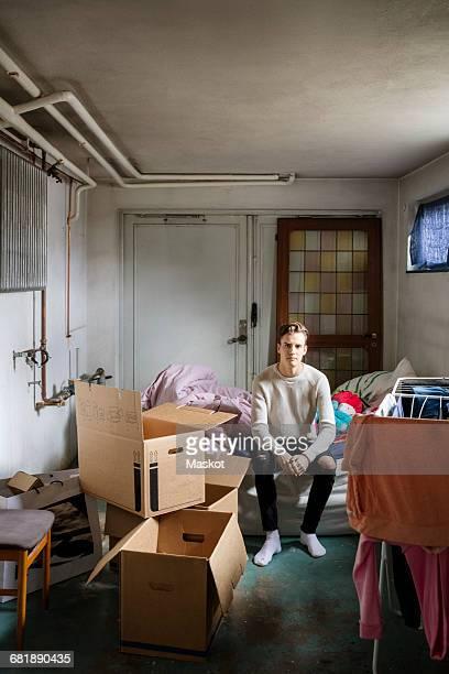 portrait of man sitting on bed at new home - 20 24 jahre stock-fotos und bilder