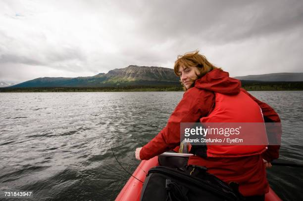 portrait of man sitting on boat in river against sky - marek stefunko stock pictures, royalty-free photos & images