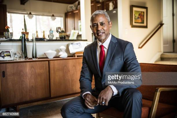 portrait of man (60yrs) sitting on chair at home - kompletter anzug stock-fotos und bilder