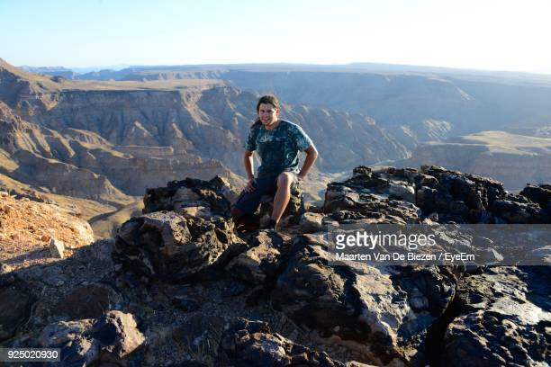 Portrait Of Man Sitting On Cliff Against Rocky Mountains