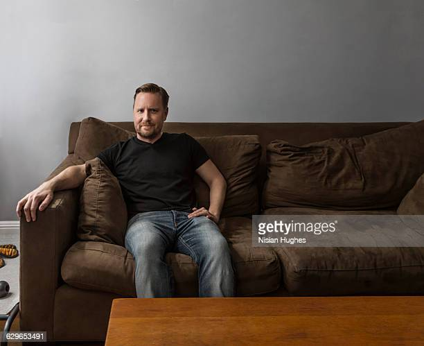 Portrait of man sitting on couch looking at camera