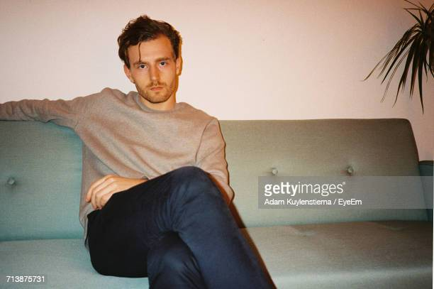 portrait of man sitting on couch - misnoegd stockfoto's en -beelden