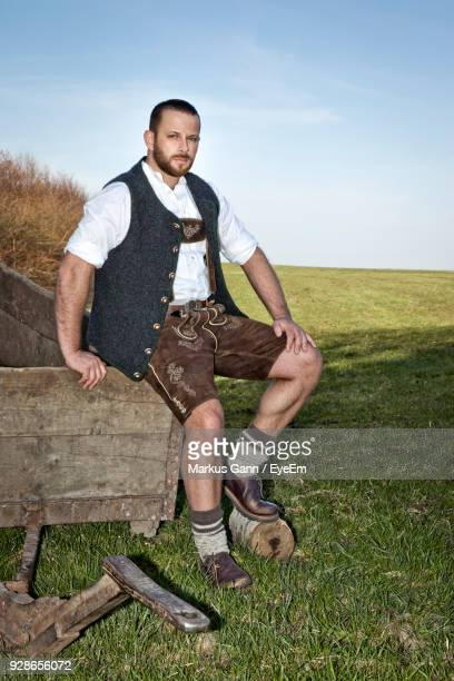 portrait of man sitting on field against sky - trough stock photos and pictures