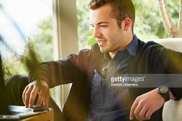 Portrait of man sitting on floor using laptop