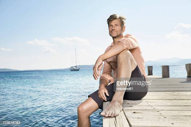 portrait of man sitting on jetty - shorts stock pictures, royalty-free photos & images