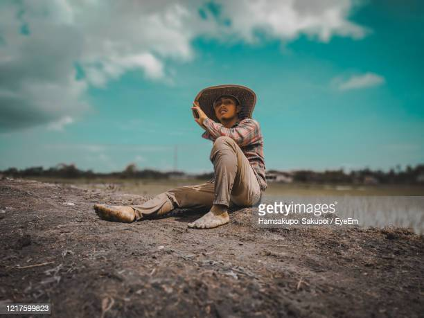 portrait of man sitting on land against sky - hamsakupoi stock pictures, royalty-free photos & images