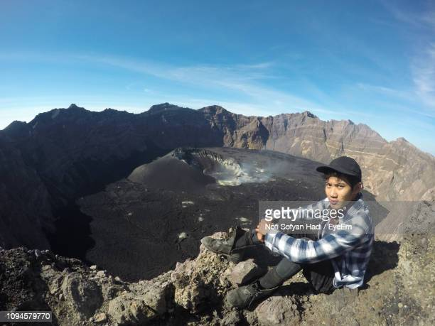 Portrait Of Man Sitting On Mountain Against Sky