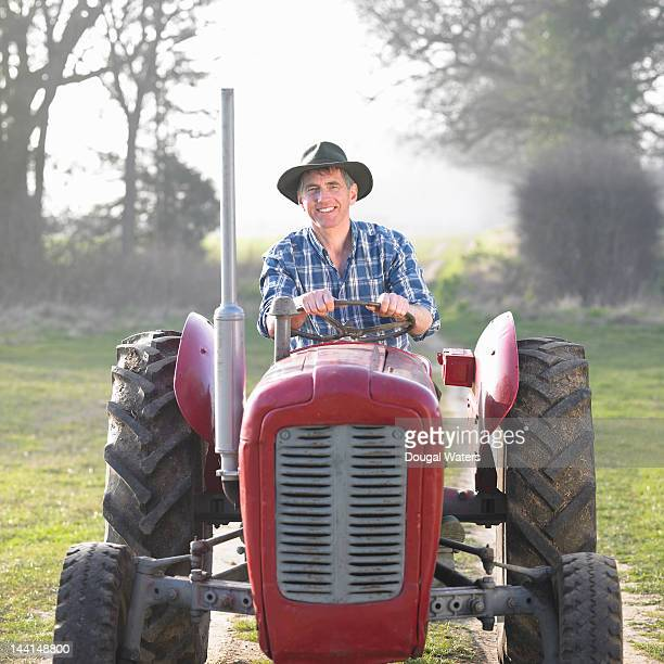 Portrait of man sitting on red vintage tractor.