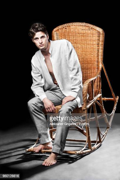 portrait of man sitting on rocking chair - rocking chair stock photos and pictures