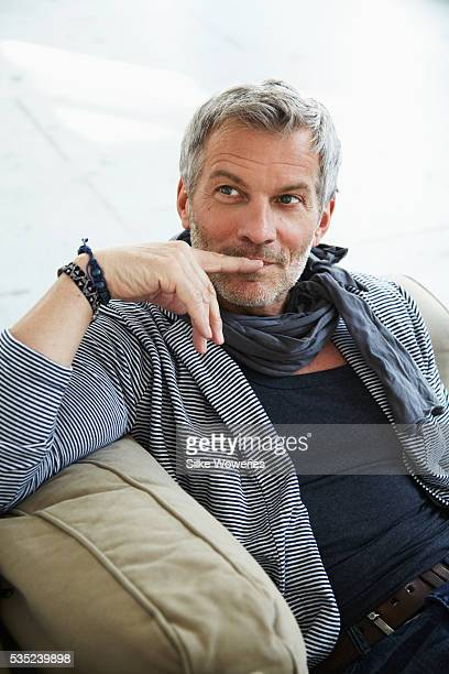 Portrait of man sitting on sofa and relaxing